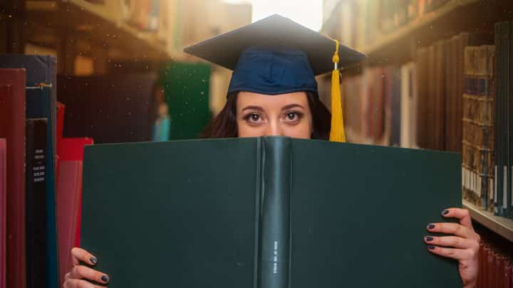 Student hidden behind book, looking prepared