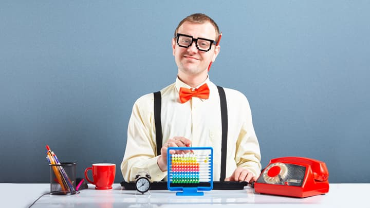 Man in glasses and red bow tie at desk with toy abacus