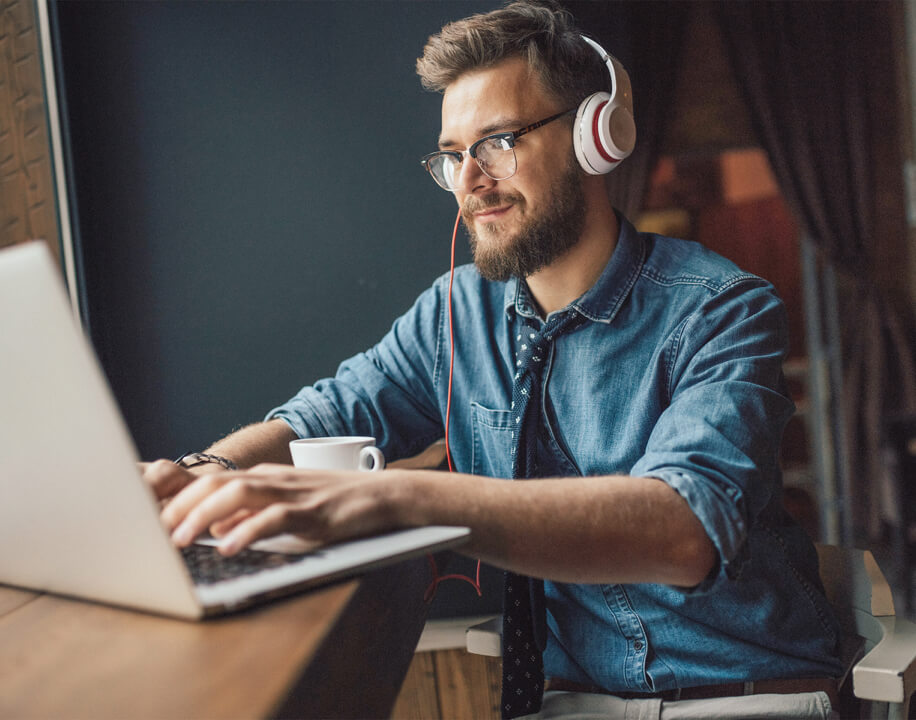 man working on a laptop with headphones on