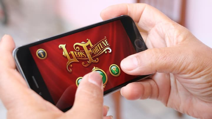 hands on mobile phone playing game