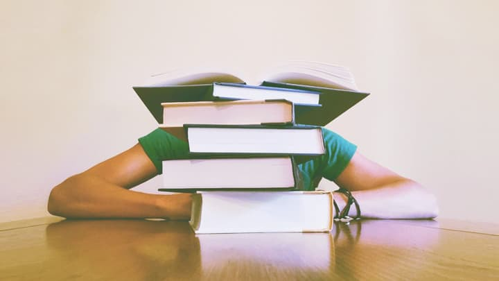 Person sitting at a table hiding behind a stack of 6 books
