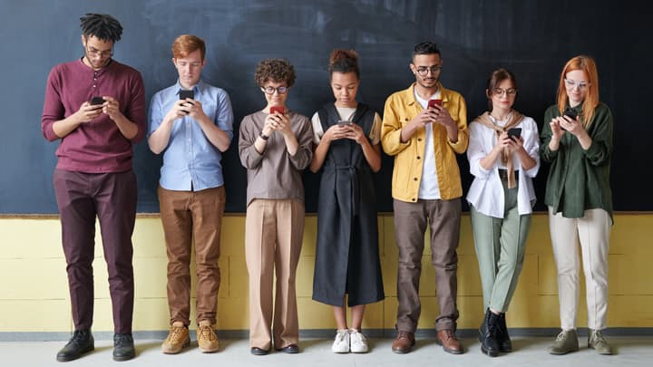 people in a line against a blackboard all looking at their mobile phones
