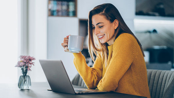 Woman drinking coffee whilst smiling at laptop