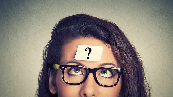 Woman with question mark post-it note stuck to her head